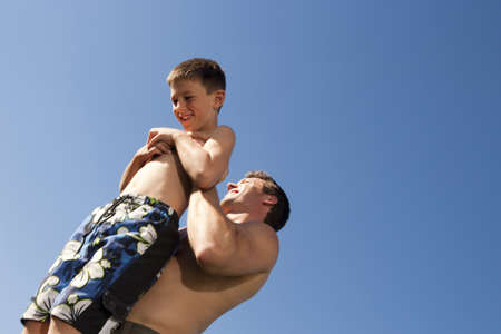 Man Holding Boy Up With Blue Sky