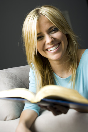 Woman With Glasses Sitting On Sofa With Book