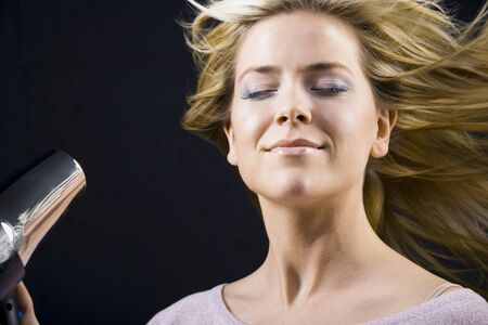 Woman Blow Drying Blonde Hair With Closed Eyes LANG_EVOIMAGES