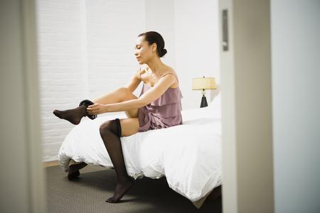 panty hose: Woman Putting On Pantyhose LANG_EVOIMAGES