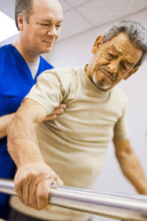 caregivers: Physical Therapist Holding A Patient While Walking