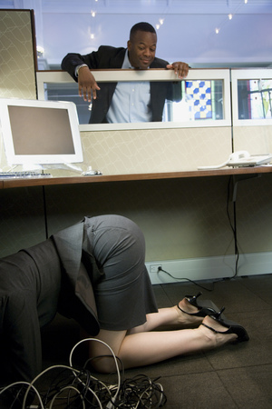 Businesswoman Crouching Under A Computer Desk With A Businessman Looking At Her