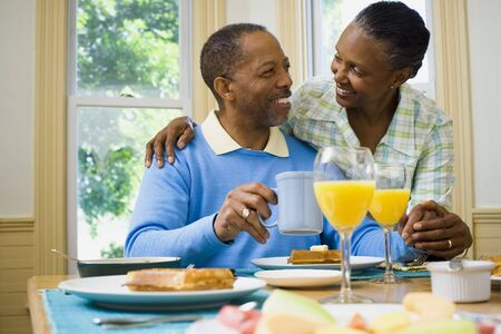chequer: Senior Man And A Senior Woman Smiling At The Breakfast Table LANG_EVOIMAGES
