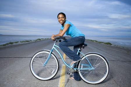Retrato de una mujer joven sentada en una bicicleta