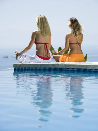 Rear View Of A Young Woman And A Mid Adult Woman Sitting In A Lotus Position At The Poolside