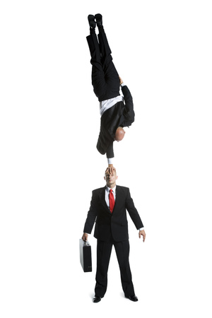High Angle View Of Two Male Acrobats In Business Suits Performing LANG_EVOIMAGES