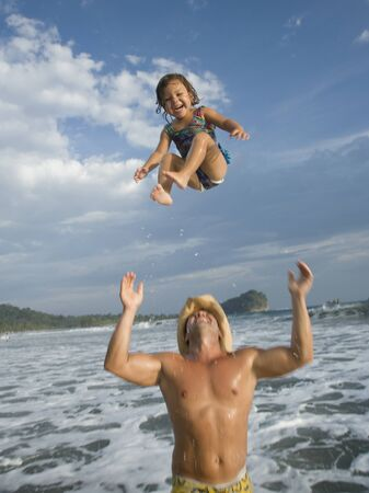 Father Tossing His Daughter In Air