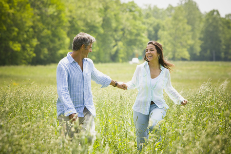 ebullient: Mature Man And A Mid Adult Woman Holding Hands And Running In A Field