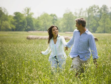 Mature Man And A Mid Adult Woman Holding Hands And Running In A Field