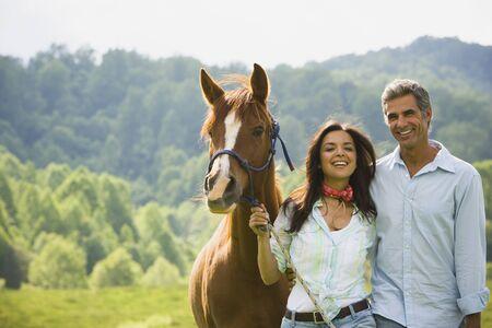 attach         â     â       ©: Retrato de un hombre y una mujer de pie con un caballo