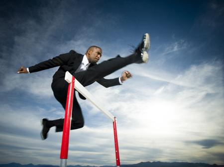 Vista de ángulo bajo de un hombre de negocios saltando sobre un obstáculo en una carrera