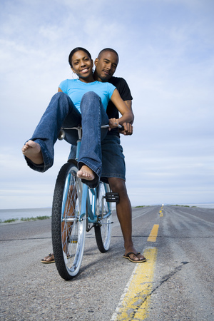Portrait Of A Young Couple Sitting On A Bicycle LANG_EVOIMAGES