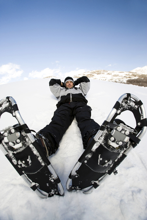 Man Resting With Snow Shoes