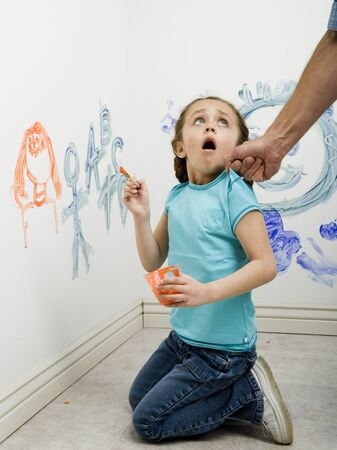 Close-Up Of A Man Pulling A GirlS Top While Painting On A Wall LANG_EVOIMAGES
