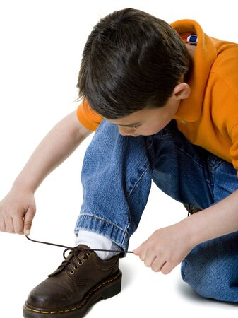 Close-Up Of A Boy Tying His Shoelace