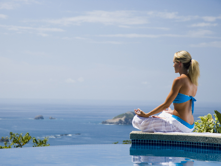 Woman Performng Yoga Exercises By Infinity Pool