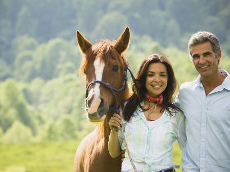 Retrato de un hombre y una mujer de pie con un caballo
