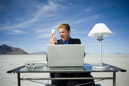 Primer plano de un empresario gritando delante de un receptor de teléfono LANG_EVOIMAGES