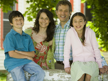 Portrait Of A Man And A Mid Adult Woman Smiling With Their Children LANG_EVOIMAGES