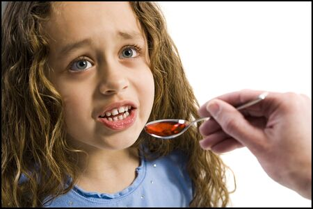Young Girl Taking A Spoonful Of Medicine LANG_EVOIMAGES