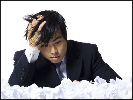 Frustrated Businessman Surrounded By Crumpled Papers