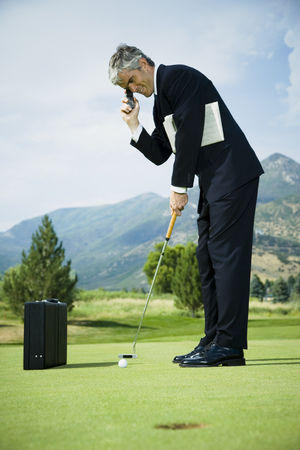 Profile Of A Businessman Playing Golf And Talking On A Mobile Phone