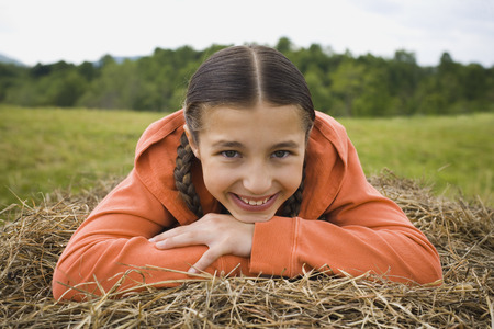 Portrait Of A Girl Leaning Over A Haystack LANG_EVOIMAGES