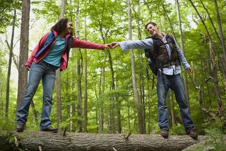 Low Angle View Of A Young Couple Holding Hands And Walking On A Fallen Tree LANG_EVOIMAGES