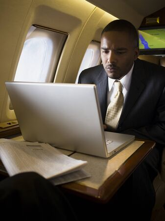 Businessman Using A Laptop In An Airplane