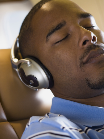 Close-Up Of A Man Listening To Music On Headphones In An Airplane LANG_EVOIMAGES