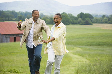 Senior Woman And A Senior Man Running In A Field