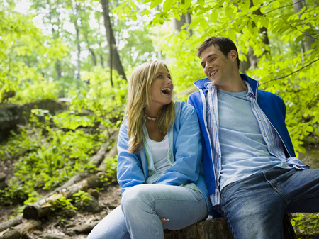 Close-Up Of A Young Couple Sitting In The Forest And Smiling
