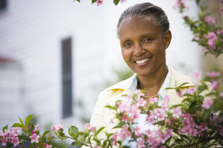 Portrait Of A Mature Woman Smiling Behind Flowers
