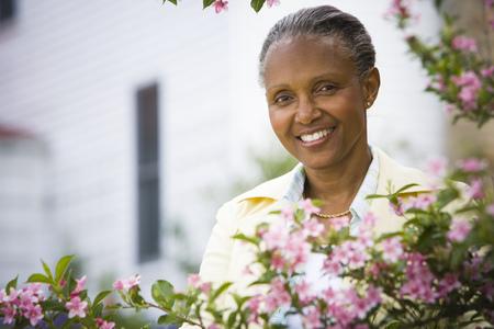 Retrato de una mujer madura sonriendo detrás de flores