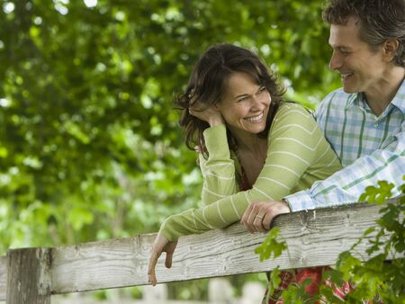 attachment: Man And A Woman Leaning On A Wooden Fence