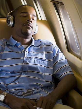 A Man Listening To Music On Headphones In An Airplane