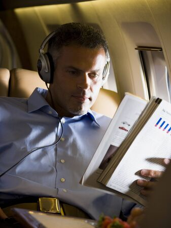A Senior Man Reading A Magazine In An Airplane LANG_EVOIMAGES