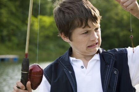 Close-Up Of A Boy Holding A Fishing Rod LANG_EVOIMAGES