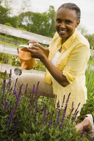 Portrait Of A Senior Woman Watering Flowers