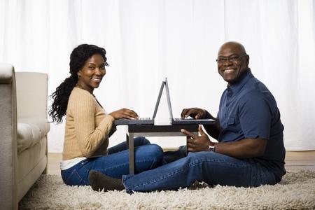 Portrait Of A Mature Couple Using Laptops