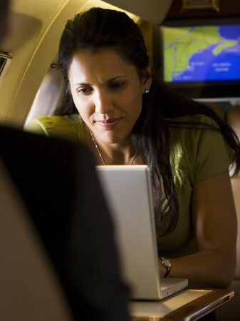 A Businesswoman Using A Laptop In An Airplane LANG_EVOIMAGES