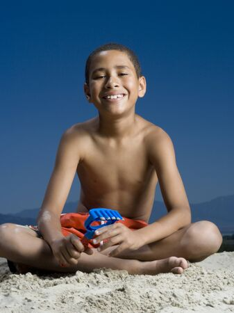 Portrait Of A Boy Sitting Beside A Sand Castle
