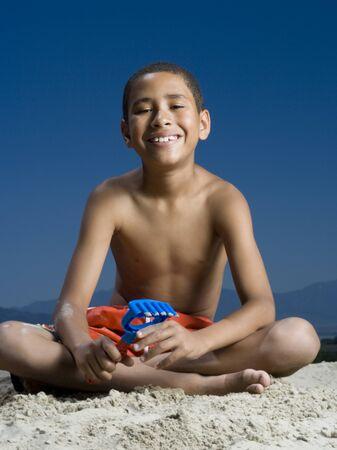 Retrato de un niño sentado al lado de un castillo de arena LANG_EVOIMAGES