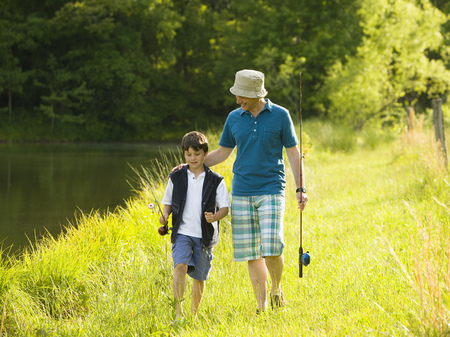 Man And His Son Holding Fishing Rods And Walking In A Forest LANG_EVOIMAGES