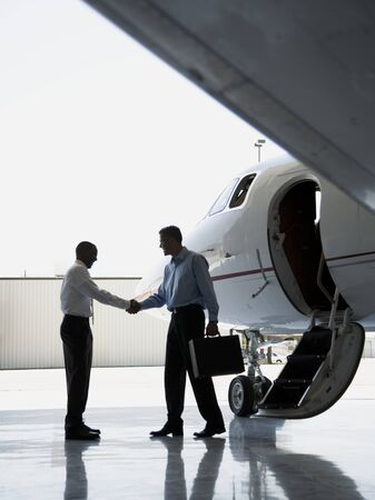 Profile Of Two Businessmen Shaking Hands Near An Airplane