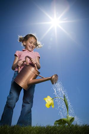 Vista de ángulo bajo de una niña regando una planta