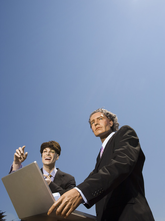 Low Angle View Of Two Mannequins Portraying Businessmen Using A Laptop LANG_EVOIMAGES