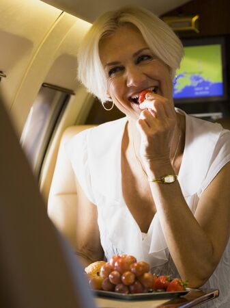 A Businesswoman Eating Fruit And Laughing In An Airplane LANG_EVOIMAGES