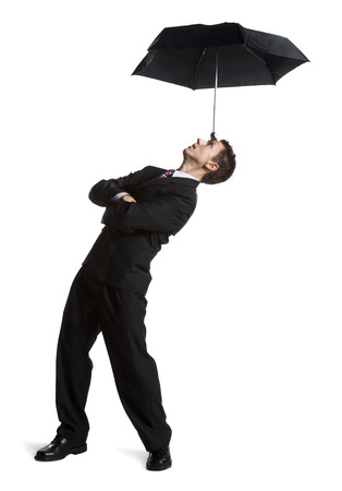 Businessman Balancing Umbrella On His Forehead