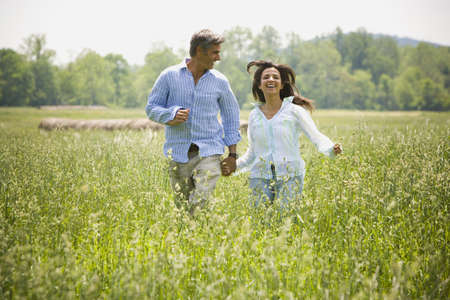 Man And A Woman Holding Hands In A Field LANG_EVOIMAGES